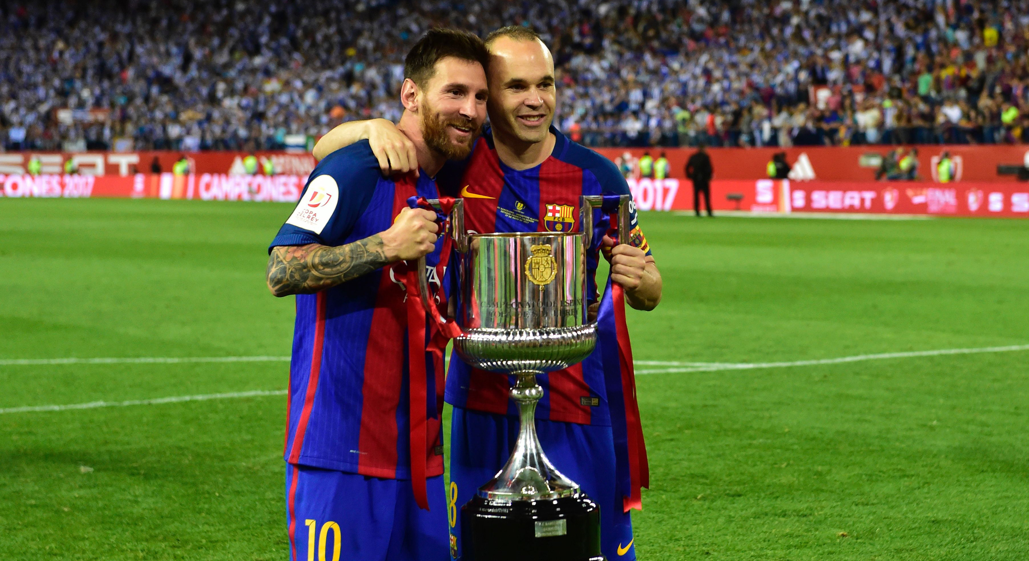 Barcelona's Argentinian forward Lionel Messi (L) and Barcelona's midfielder Andres Iniesta hold up the trophy after the team won the Spanish Copa del Rey (King's Cup) final football match FC Barcelona vs Deportivo Alaves at the Vicente Calderon stadi